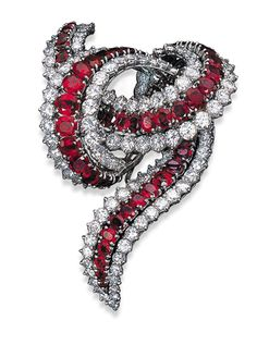 A RUBY AND DIAMOND CLIP BROOCH Designed as oval-cut ruby and circular-cut diamond interlaced scrolls RETAILED by Cartier in 1967. (=)