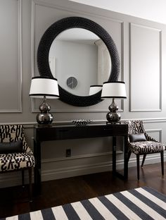 moldings | entry decor ideas | black and white color scheme | striped rug | round mirror | accent chairs