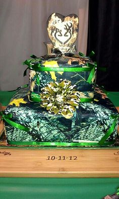 Camouflage wedding cake with an orange flower and ribbon.....just needs to br orangr ribbon