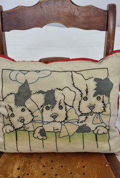 Adorable Embroidered Pillow of a puppy trio decked out with bows peeking over a fence! Measures approximately 16 x 13 1/2. Embroidered linen