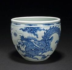 A blue and white porcelain plant. Kangxi Period. Photo Bonhams    Form of fish bowl year with elongated cloud filling the tiny waist Beneath the rolled rim and a single dragon chasing flaming pearl has amid clouds across icts curving walls, the base unglazed,