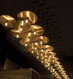 Lighting concept for Al Dente Restaurant brass discs carrying light