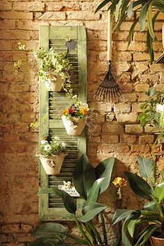 Its an old window shutter repurposed as a garden wall hanger! Adds real character to the space.  Would be cute on either side of a lattice backsplash for our cider block outdoor bar!
