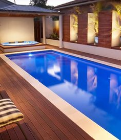 Deep Blue rectangular pool heading up towards a day bed! Light paved edge with decked finish around pool