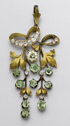 GOLD, DEMANTOID GARNET AND DIAMOND GRAPE CLUSTER BROOCH, RUSSIAN, EARLY 20TH CENTURY.  The articulated motif decorated with 9 round and cushion-shaped demantoid garnets representing grapes, further accented with 1 old European-cut diamond of yellow tint and 15 small old European-cut diamonds, Russian assay marks. With fitted case.