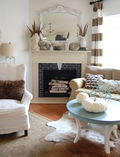 gorgeous & calming arrangement & color palette of furniture, cow hide rug, birch logs, faux fur throw pillow, vintage mantle mirror along with curtains.