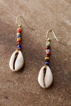 Multicolored cowrie shell drop earrings made using colorful African glass beads and wiring. These earrings measure about 2 (inches) in length and are very lightweight Seashell Jewelry, Cute Jewelry, Boho Jewelry, Jewelry Crafts, Beaded Jewelry, Clean Jewelry, Fashion Jewelry, Country Jewelry, Cowgirl Jewelry
