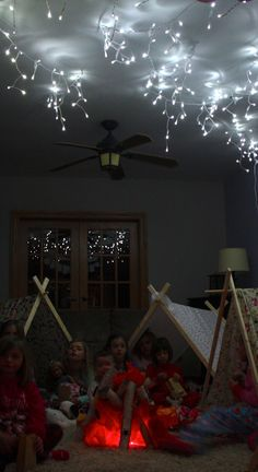 indoor camping under the stars - Beth Kruse Custom Creations. This fake fire is such a cute indoor party idea. She used red and orange tissue paper, and logs, and red rope lights from Hobby Lobby.