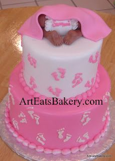 Two tier pink and white girl's baby shower cake with footprints and baby bottom topper