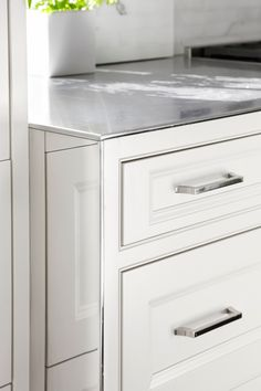 Interesting with a clean, simple look: Countertop wrapped in stainless steel with a whisper-thin edge. The use of a mirror on the side of the cabinetry adds light and interest in what might be an otherwise awkward transition.