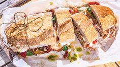 Gjør det superenkelt på piknik ved å lage et helt lite brød om til en stor sandwich, smurt med hvitløksmajones og fylt opp med godsaker som soltørkede tomater, grillet paprika, fersk mozzarella og spekeskinke.     Tips: Bind gjerne sandwichen sammen med litt kjøkkenhyssing slik at alt holder seg på plass.      Grillet paprika kan kjøpes ferdig i litt ulike varianter, eller du kan lage det selv. Grill paprikaen over grill, eller i en grillpanne, til skinnet blir helt svart. Ha paprikaen over… Mozzarella, Pesto, Camembert Cheese, Sandwiches, Lunch, Recipes, Red Peppers, Lunches, Recipies