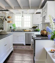 From its exposed joists to uneven, wide-plank floors, the bright, updated kitchen in this Connecticut farmhouse still retains much of its historic charm.