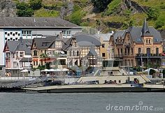 Picture taken along the Rhine valley in Germany. In the picture we see the great river Rhine, on whose waters is moored on the opposite shore, a large boat. Besides the boat you can see the houses lined up in a small town. At the end of the village and at the foot of the rocky hill you see a big white building.
