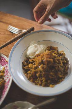 Ingredientes para dos personas   4 cucharadas de aceite de oliva, 2 cebollas medianas en rodajas finas, 125 gr de lentejas pardinas, 100 gr de arroz basmati, 1 cucharadita de semillas de comino, 1 cucharadita de semillas de cilantro, media cucharadita de cúrcuma molida, media cucharadita de pimienta de Jamaica, media cucharadita de canela molida, media cucharadita de azúcar moreno, sal y pimienta.