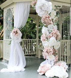 White curtain and large flowers made from material cloth. Large statement.