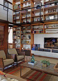 Na sala de estar, a estante de cumaru (Marcenaria Scholl) ocupa o pé-direito duplo e é equipada com passarela metálica. Poltronas de madeira, couro e sarja (Armando Cerello) circundam a mesa de centro, de aço cortén e madeira de demolição (Giacomini).