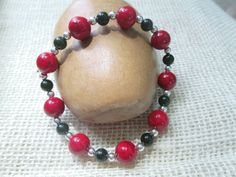 This lovely red, black and silver stretch bracelet is part of a set.  It would be lovely worn together with the matching necklace and earrings, or separately.  It would be ...