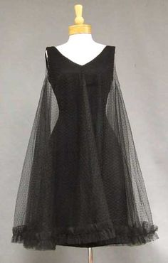 From Vintageous. A wonderfully flirty 1960's cocktail dress. Fitted black crepe dress has an attached black point d'esprit tulle trapeze overlayer with ruffled hem.
