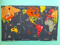 Hand-sewn vintage burlap and felt world map with charm embellishments.