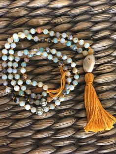 ** witchhearthandmade ** In the colours of sand and sky, conjuring images of both the desert and the beach, this beautiful mala is made of multi coloured amazonite on a mustard coloured cotton with a handmade tassel, jasper guru bead and alloy feature beads. Perfect for boho babes, yoga fanatics and