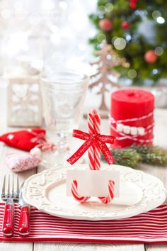 Table de Noël : idées de déco facile pour table de fête, comme ces marque-place avec des sucres d'orge de fêtes, rouges et blancs. / / / / #tabledefete #table #fêtes #noel #reveillon #deco #décoration #rouge #blanc #sucredorge #marqueplace #diy #facile #aufeminin #ellehabitela