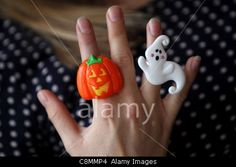 A young girl pictured wearing a tacky plastic Halloween Pumpkin and a Ghost ring in Hove, East Sussex, UK.© Sam Stephenson / Alamy