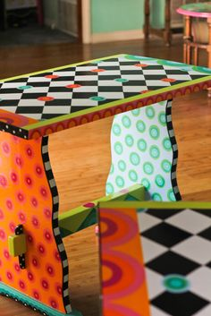 Trestle table in bright colors with black and white checked top. Acrylic finished with glossy polyurethane. Rebecca Waring-Crane.