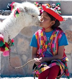 Little girl getting kisses from her alpaca in Peru.