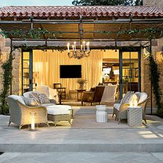 Rear Terraces & Courtyard | A wrought iron pergola lends structure to an outdoor seating area, with a charming spot for climbing roses to grow overhead. | SouthernLiving.com | #SLIdeaHouse | Architect: Michael G. Imber Architects and Interior Design: Mohon-Imber Interiors