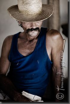 A Cuban laborer rests in the shade    Keywords: Stock Photo Picture Cuba Cuban Spanish Speaking Countries Latin America Trinidad Sancti Spíritus Vertical Guajiro Cowboy Hat Desaturated Latin American Cowboy Looking down Man Tranquil Rustic Earth Tones Moustache Sancti Spiritus Straw Hat Laborer Rest Shade Male Portrait