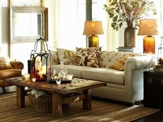 Farmhouse living (Hastings reclaimed wood coffee table, twill white linen chesterfield sofa, plaid & nature scene pillows, rustic milk tin flower vase, lanterns, leather chair, painted mirror, explorer trunk