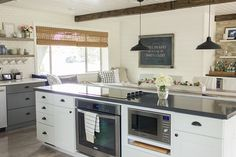 gray shaker kitchen cabinets, bronze bin handles, white shaker cabinets on island with bronze bin cup handles, urban c chic