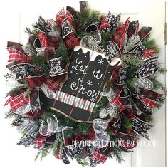 Large Christmas or Winter wreath made on pine wreath base and white snowball mesh ruffles and premium red and black striped mesh ruffles for added fullness. There are ribbon strips of plaid, black with white seasonal words, and black with red and white glittery snowflakes. There