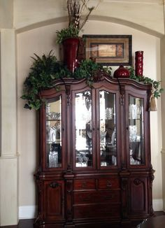 China cabinet decoration -- I would use different colors, but I like the varied heights. Add lights to the greens? Top Of Cabinet Decor, China Cabinet Decor, Decorating Above Kitchen Cabinets, Kitchen Cabinet Design, Kitchen Decor, Top Of Cabinets, Above Cabinets, China Cabinets, Grey Cabinets