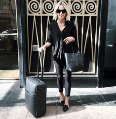 Jacey Duprie wears a button-down top, cropped jeans, flats, black sunglasses, and a tote bag