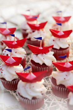 Idées de cupcakes avec des petits bateaux rouges à servir en dessert pour un mariage au bord de l'eau.