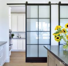 Custom iron doors, hung on an industrial track, hide the food and butler's pantries. They give the kitchen a modern edge, perfect for a space that leans toward minimalism. White cabinetry designed by Bellacasa Design Associates and built by Windstone Partners keeps the area crisp and sleek.