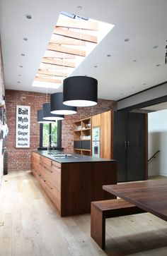 The long space allowed for a 16-foot island, perfect for family cooking and entertaining.  Drawers on both sides.  Love the exposed brick and the interesting ceiling window.  The refrigerator doors are cladded hot-rolled steel.  Pots hung on wall - above the pots are jars of grains, nuts, etc on a shelf.  Love love love - check out dining area too.  Fascinating preservation of former Carnegie Library