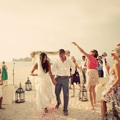Simple beach setting with an arch, fresh flower petals and surrounded by friends and family #LuxBride
