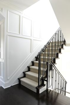 Incredible traditional millwork runs up this stairwell wall and continues down the hallway. The soft white walls contrast against the ebony floors and iron stair railings. A neutral stair runner creates softness under foot up the stairway. Stair Railing Design, Iron Stair Railing, Stair Decor, Staircase Railings, Staircases, Banisters, Stair Treads, Iron Spindles, Staircase Molding