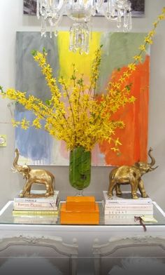 A touch of color. Classic furniture with and abstrac oleo by kerri Rosenthal, and glass vase with green leaves and yellow flowers in.