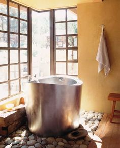 Adorable Bathrooms With Japanese Soaking Tub : Rustic Bathroom Design Idea With Silver Finished Japanese Soaking Tub And Taupe Wall Paint Color Also Natural Stones Also Wooden Chair And Glass Windows Also Coat Hangers For Towel