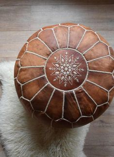 · This authentic Moroccan Cognac Brown pouf is made of genuine natural leather. Individual pieces of leather are dyed, stitched together and then decorated with intricate hand-sewing. Pouf Ottoman, Pouf Chair, Moroccan Leather Pouf, Moroccan Pouf, Moroccan Decor, Living Room Carpet, Rugs In Living Room, Bedroom Gadgets, Handmade Ottomans