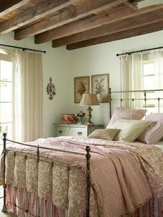 Soft pink linens from Elizabeth Allen Atelier pair with an antique quilt atop a tag-sale iron bed.