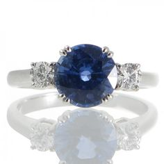 An 18ct white gold ring featuring a 2.28ct round colour change Sri Lankan sapphire changing from blue to purple accompanied by a GRS certificate set in four split claws between a pair of round brilliant cut diamonds totaling 0.30ct graded as colour G-H clarity VS each set in four claws above a railed gallery all to a plain polished band. #Rutherford #Melbourne