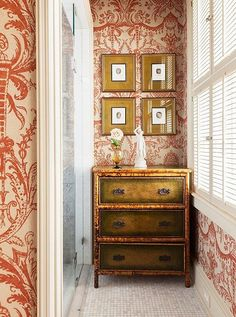 """A powder room was redone with a swirling red-and-white wallpaper to mirror the pops of red throughout the rest of the house and filled with burnished brass and gilded furniture topped with classical white objects d'arte in bright whites for a subtle contrast. See fine-jewelry designer Elizabeth Locke's full home tour in """"A Stunning Estate with Southern Grace and Italian Romance"""" over on our Style Guide!"""