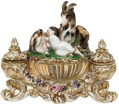 A JACOB PETIT PORCELAIN FIGURAL ENCRIER  MID 19TH CENTURY, BLUE J.P. MARK  Of neo-Rococo form, the cover modeled as a recumbent goat and infant before a tree-stump quill holder on a rocky mound, the interior of the box painted with a female goat herder reserved on a gilt sablé ground, set above a broad shell and flanked by two scroll molded covered wells with ink and sander inserts, the lower body painted with a garland of flowers on a richly gilt ground 12½ in. ( 31.7 cm.) long (6)