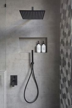 In this modern bathroom the shower has a matte black rainfall shower head and a hand held shower head as well as a tiled built-in shelf.