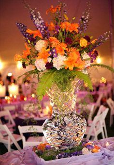 Brides: Purple and Orange Wedding Centerpiece. An ice sculpture vase filled with purple delphinium, orange Asiatic lilies, purple iris, Milva roses, eggplant carnations, lavender hydrangea and sword fern added a unique element to the reception.