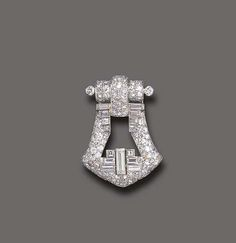 AN ART DECO DIAMOND CLIP BROOCH, BY CARTIER -  Of geometric design, the openwork circular and baguette-cut diamond clip brooch, mounted in white gold, circa 1930